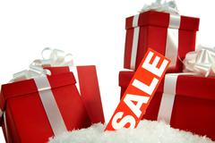 a heap of christmas gifts in snow with sale tag near by - stock photo
