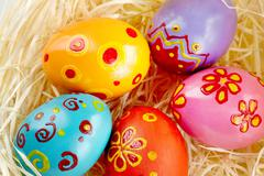 Close-up of colored and decorated easter eggs in straw Stock Photos