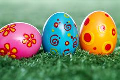 Row of colored and decorated easter eggs in grass Stock Photos