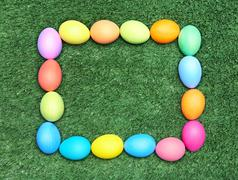 image of multicolored eggs forming a square over green grass - stock photo