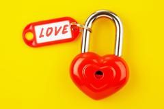 Image of red lock with love label on a yellow background Stock Photos