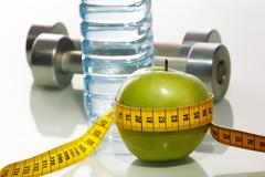 Close–up of green apple with measuring tape and two metal barbells on background Stock Photos