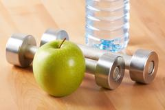 Close–up of green apple with plastic bottle and two metal barbells on background Stock Photos
