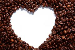 Image of coffee beans forming shape of heart on white background Stock Photos