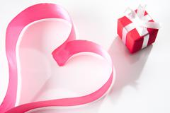 Form of heart made up of pink ribbon with small giftbox near by Stock Photos