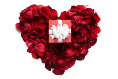 Red rose petals making up heart with small giftbox on it Stock Photos