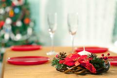 image of holiday wreath with flutes and plates at background on christmas table - stock photo