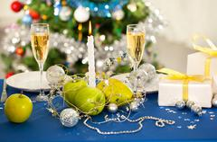 Image of holiday table with flutes of champagne, fruits, gifts, candle and plate Stock Photos