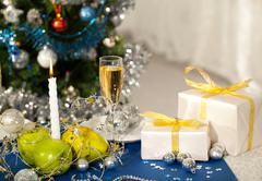 image of holiday table with flute of champagne, fruits, gifts, burning candle an - stock photo
