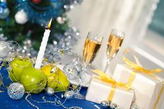 image of holiday table with flutes of champagne, fruits, gifts, burning candle a - stock photo