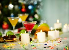 Image of holiday objects: cocktails, burning candles and christmas decorations Stock Photos