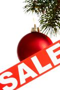 Red christmas bauble on coniferous branch and sale tag near by Stock Photos