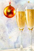 Two champagne flutes with ball on firtree branch behind Stock Photos