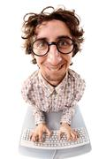 fish-eye shot of a smiling tousled nerd typing on the keyboard - stock photo