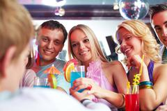 Photo of pretty girls looking at barman with guys near by Stock Photos