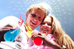 below angle of cheerful couple with cocktails looking at camera - stock photo