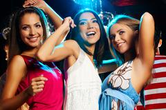 Group of fashionable girls dancing energetically in night club Stock Photos