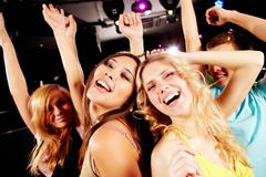Two joyful girls dancing in night club and having fun Stock Photos