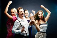 four joyful friends dancing together - stock photo