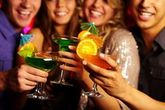 Close-up of several cocktails in young people hands Stock Photos