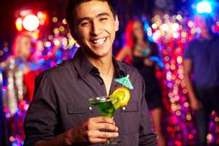 Image of happy guy holding cocktail at party Stock Photos