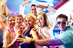 portrait of glamorous girls dancing at party with happy friends near by - stock photo