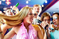 portrait of joyous girl singing at party on background of happy friends - stock photo