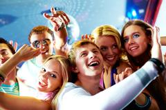 portrait of glad guy dancing at party and laughing with friends on background - stock photo