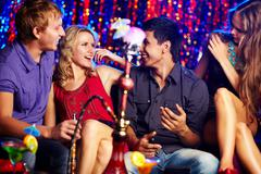 Image of two happy couples interacting in night club Stock Photos