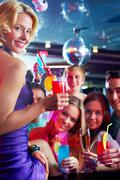 portrait of cheerful girl with cocktail looking at camera with friends on backgr - stock photo