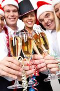 Image of crystal glasses full of champagne held by happy business people Stock Photos