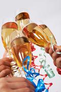 close-up of flutes of golden champagne being clinked during toast - stock photo