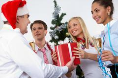 image of cheering associates taking gifts from ceo in santa cap at corporate par - stock photo