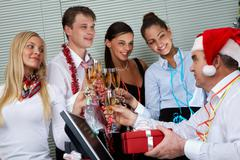 Image of cheering associates congratulating ceo in santa cap at corporate party Stock Photos