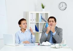 image of businessman sneezing while his partner looking at him with anxiety in o - stock photo
