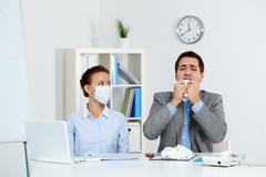 Image of sick businessman with tissue sneezing with his colleague in mask sittin Stock Photos