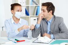 Image of sick businessman with tissue looking at his colleague in mask dissolvin Stock Photos