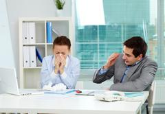 image of businesswoman sneezing while her partner looking at her unsurely in off - stock photo