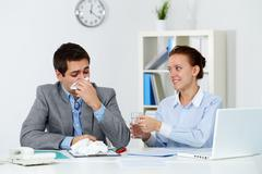 Image of businessman sneezing while his partner giving him tablets and water in Stock Photos