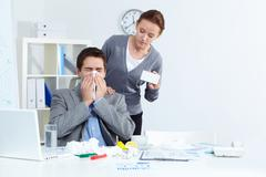 image of ill businessman sneezing while his partner offering him good medicine i - stock photo