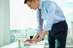 portrait of confident man at workplace typing on laptop - stock photo