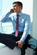 portrait of handsome man calling by mobile phone in office - stock photo