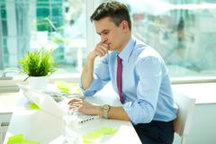 portrait of pensive man typing in office - stock photo