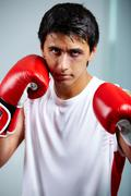 Image of a boxer in red gloves ready to attack his rival Stock Photos
