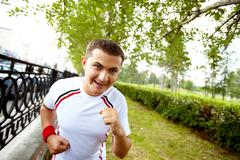 Image of happy young sportsman running in park Stock Photos