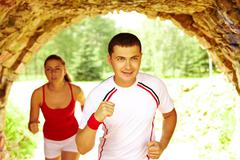 Image of happy young sportsman running with his girlfriend Stock Photos