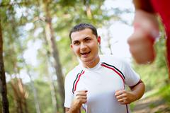 Image of happy young sportsman with earphones running in park Stock Photos