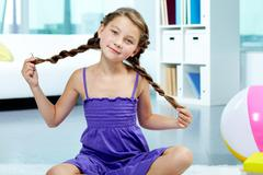 portrait of young smiling child in violet dress posing in front of camera - stock photo