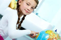 portrait of cute child with globe looking at camera - stock photo