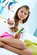 Stock Photo of portrait of lovely girl holding colorful pencils